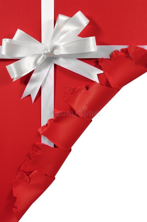 Natale o arco bianco del nastro del regalo del raso di compleanno su fondo di carta rosso aperto lacerato fotografia stock libera da diritti