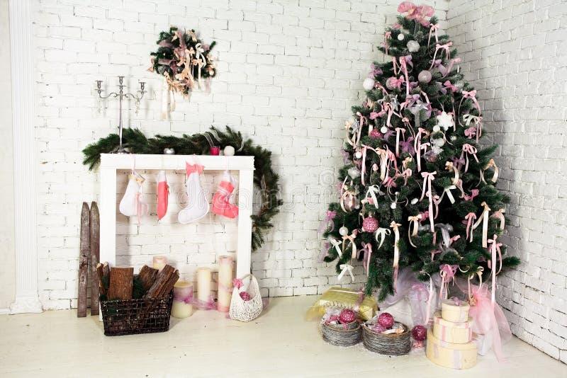Natale piacevole interno con un albero, un camino ed i regali di abete immagini stock