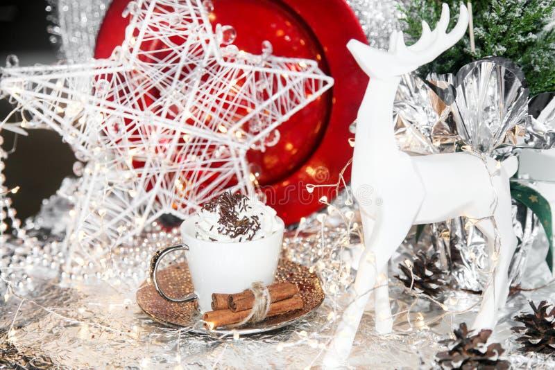 Natale rosso e bianco, renna di natale, tazza di panna montata, piatto rosso, palle di natale, cono di inverno su fondo bianco, c fotografia stock