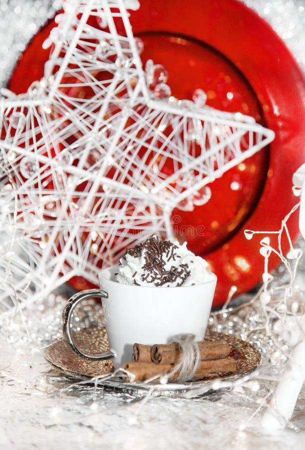 Natale rosso e bianco, renna di natale, tazza di panna montata, piatto rosso, palle di natale, cono di inverno su fondo bianco, c fotografie stock libere da diritti