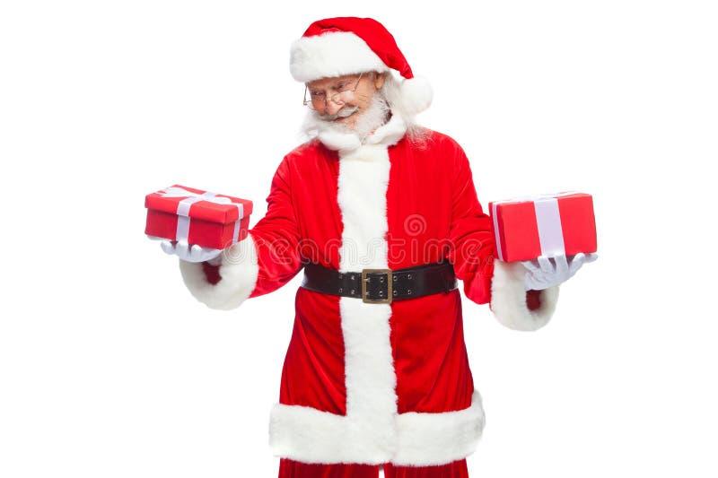 Natale Santa Claus sorridente in guanti bianchi tiene due scatole con i regali Il concetto di scelta del regalo, generoso fotografia stock