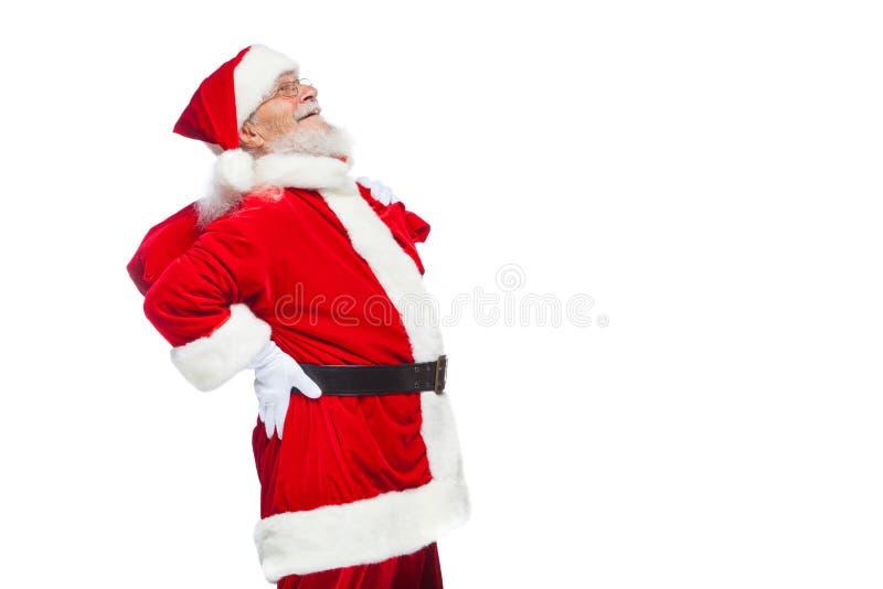 Natale Santa Claus sta soffrendo dal dolore alla schiena e tiene una borsa rossa con i regali sul suo indietro Isolato su bianco immagine stock libera da diritti