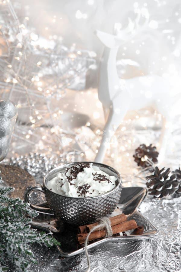 Natale, tazza d'argento di natale di panna montata sul piatto brillante, renna bianca e fondo metallico, con i dolci, cannella, i fotografie stock libere da diritti