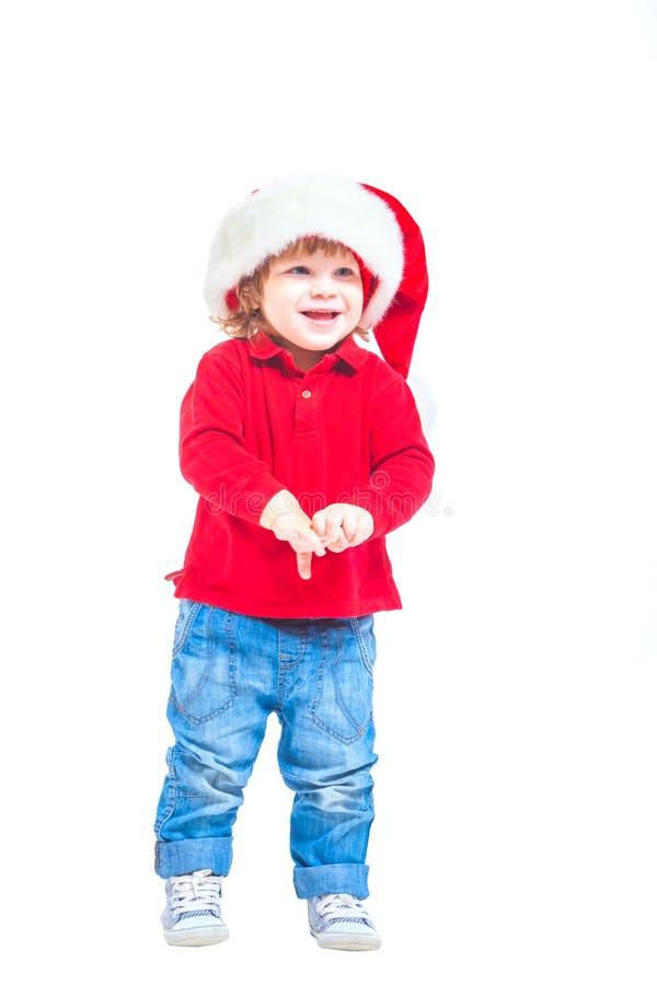 Natale Un ragazzino in un cappello di Santa, in rivestimento rosso e blue jeans Isolato su priorità bassa bianca fotografia stock