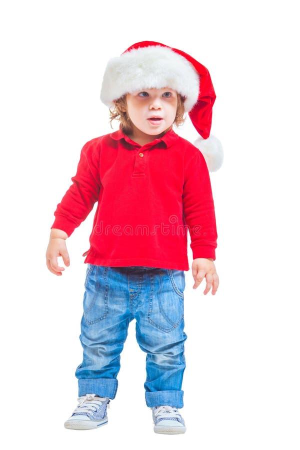 Natale Un ragazzino in un cappello di Santa, in rivestimento rosso e blue jeans Isolato su priorità bassa bianca immagine stock libera da diritti