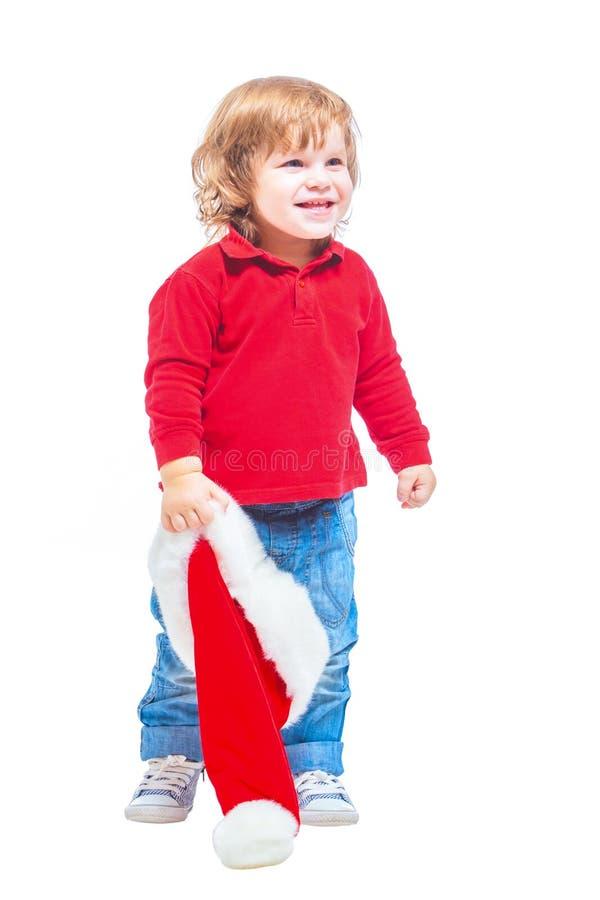 Natale Un ragazzino in un cappello di Santa, in rivestimento rosso e blue jeans Isolato su priorità bassa bianca fotografie stock libere da diritti