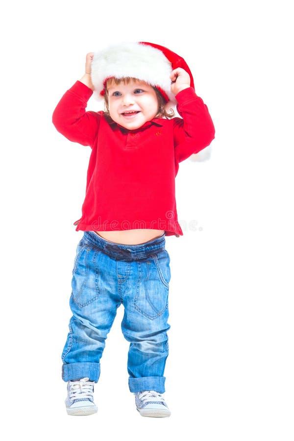 Natale Un ragazzino in un cappello di Santa, in rivestimento rosso e blue jeans Isolato su priorità bassa bianca fotografie stock