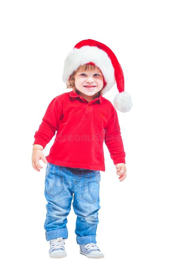 Natale Un ragazzino in un cappello di Santa, in rivestimento rosso e blue jeans Isolato su priorità bassa bianca immagini stock libere da diritti