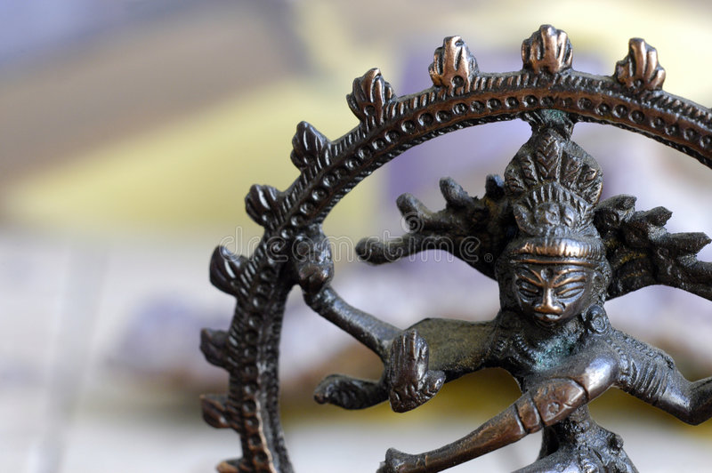 Nataraja Statuette. A partial view of a small bronze statue of of the Hindu Deity of Shiva in the form of Nataraja, king of the Dance. The background is entirely stock photo
