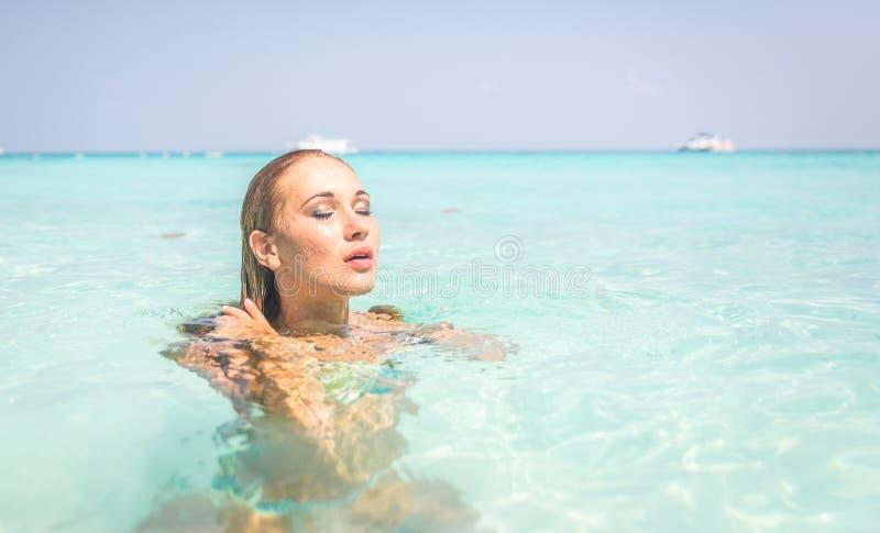 Natation de femme dans l'eau bleue photo libre de droits