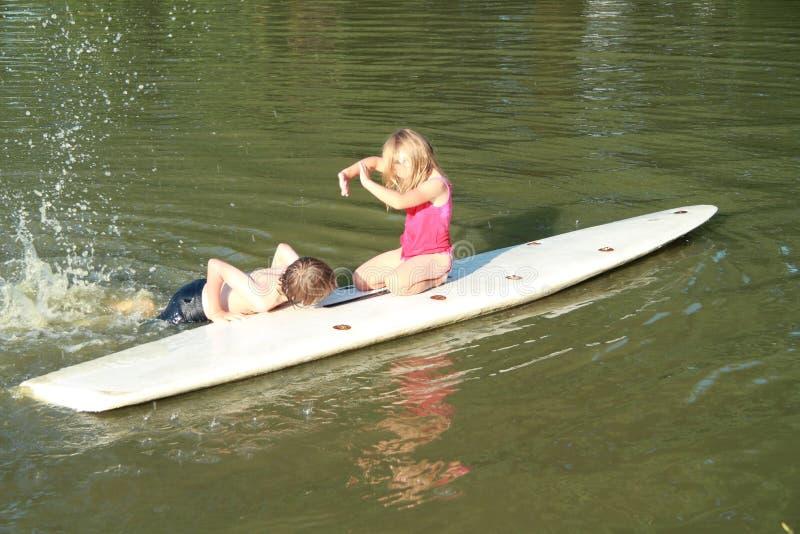 Natation de garçon par une vague déferlante avec la fille photo stock