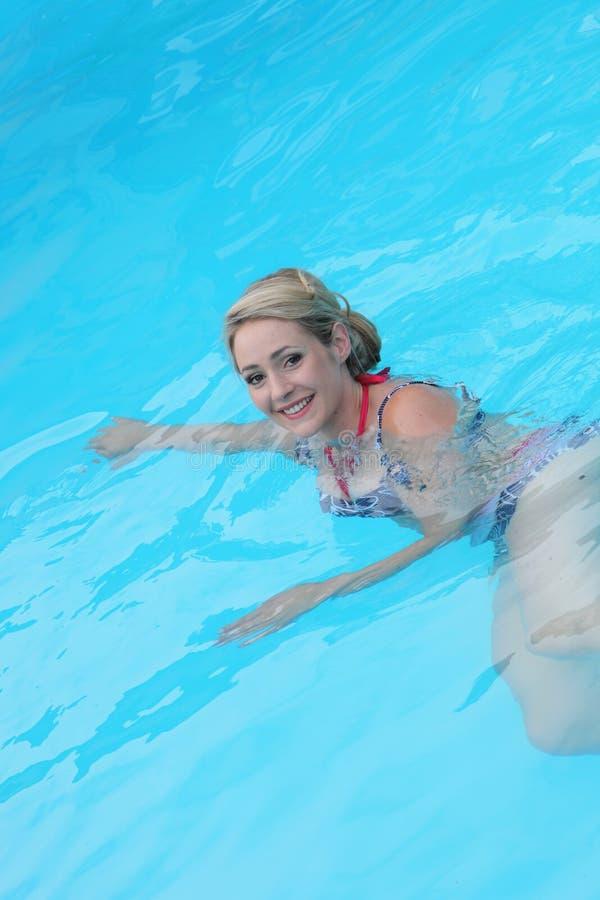 Natation de jeune femme dans la piscine photo libre de droits