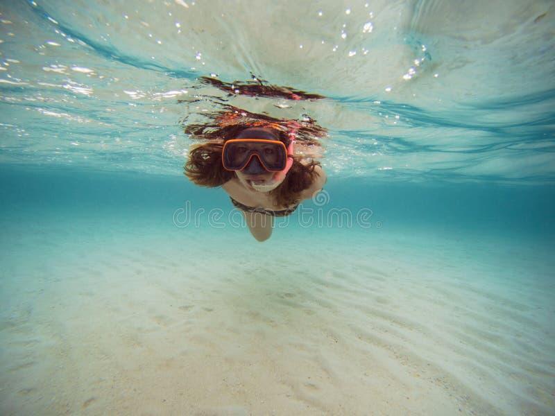Natation de jeune femme et naviguer au schnorchel avec le masque et les ailerons dans l'eau bleue claire photos stock