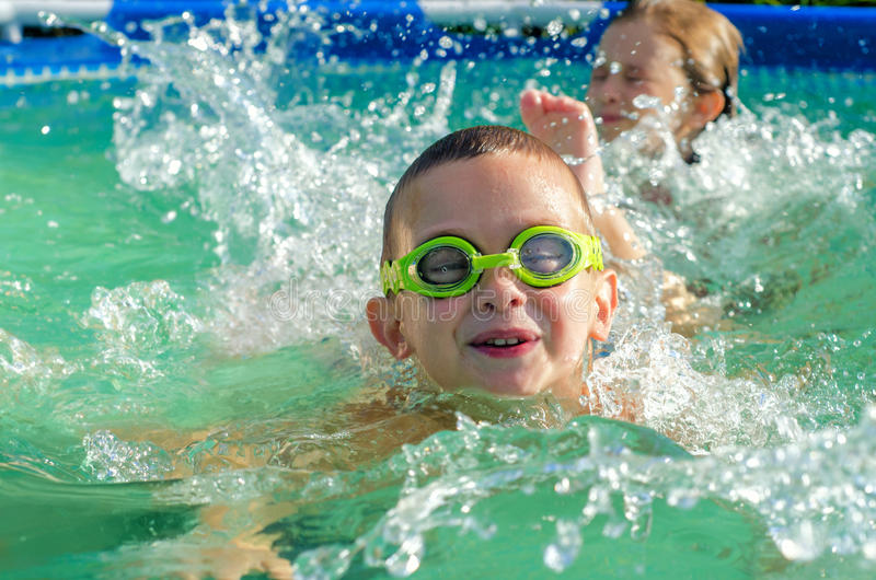 Natation de petit garçon et de fille dans la piscine le jour ensoleillé d'été images stock