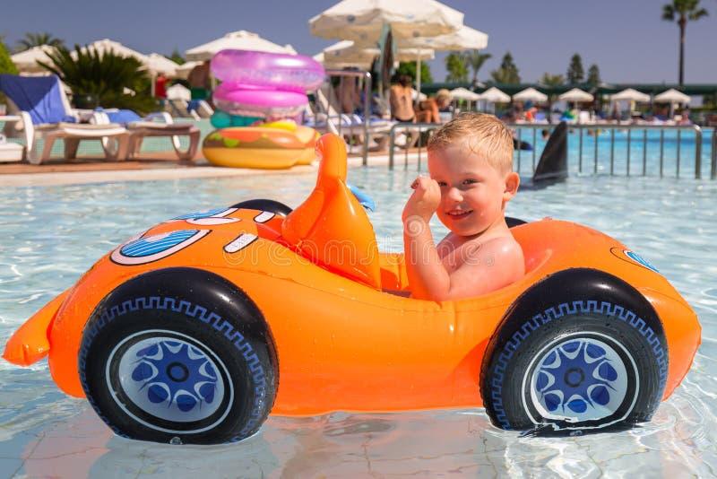 Natation heureuse de petit gar?on dans la voiture gonflable des vacances d'?t? images stock