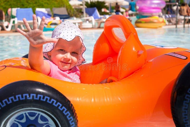 Natation heureuse de petite fille dans la voiture gonflable des vacances d'?t? photos stock
