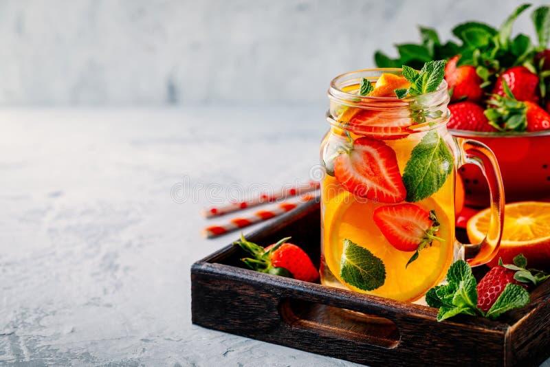 Natchnąca detox woda z pomarańcze, truskawką i mennicą, Lód - zimny lato koktajl, lemoniada lub zdjęcia stock