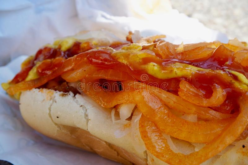 Nathan`s hot dog close up with toppings. Shows onions, ketchup, mustard, and hot dog bun. Coney Island, NY stock images