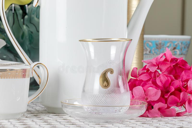 National Azerbaijani glass of armudu tea on a saucer with a national pattern Buta in the middle, against a white ceramic teapot. stock image