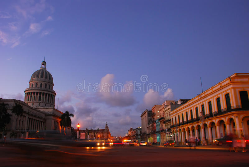 National Capital Building and opposite Shop houses. In Havana Cuba at Dusk with moving traffic taken from middle of the road stock photos