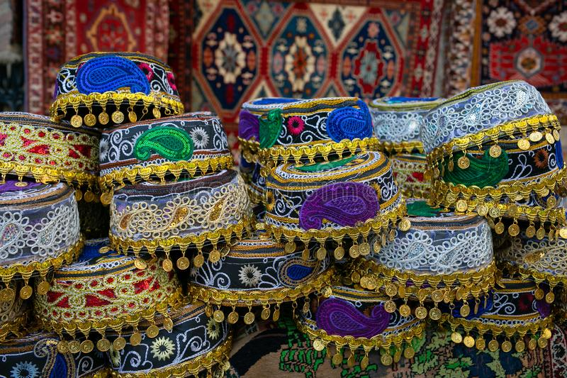 National colored headwear with national patterns of Buta on the background of carpets with national paintings. stock image