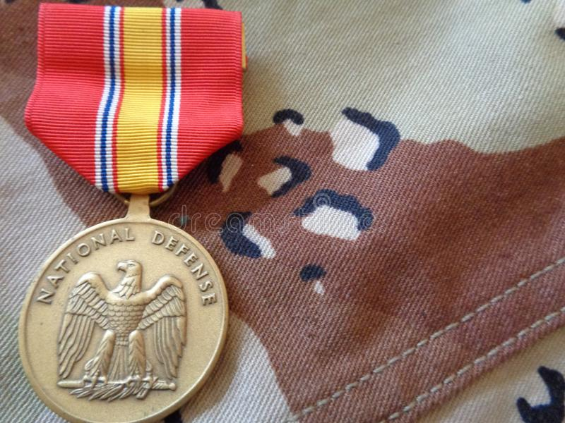 National Defense Medal on Chocolate Chip Uniform. The National Defense Service Medal is laid out over the desert camouflage uniform, or DCU, used during Desert stock photos