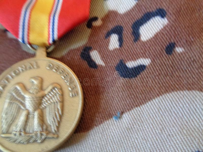 National Defense Service Medal Against BDU. The National Defense Service Medal is laid out on the woodland camouflage uniform the Army used in the 1990s. The stock images
