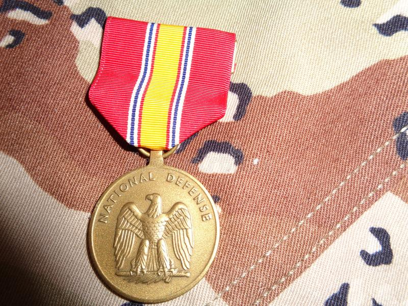 National Defense Service Medal Against DCU. The National Defense Service Medal is laid out on the desert camouflage uniform the Army used during Desert Storm stock photography