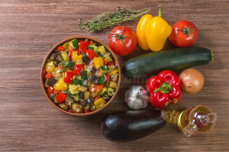 Provencal dish Ratatouille with ingredients for cooking in a pot made of ceramics on the table made of oak planks. Brown. Proper n. National dish of French royalty free stock photography