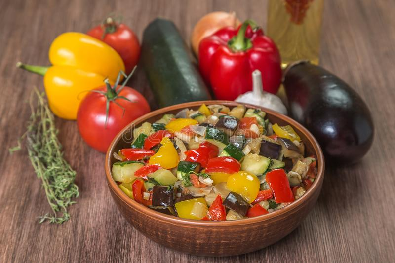 Provencal dish Ratatouille with ingredients for cooking in a pot made of ceramics on the table made of oak planks. Brown. Proper n stock photography