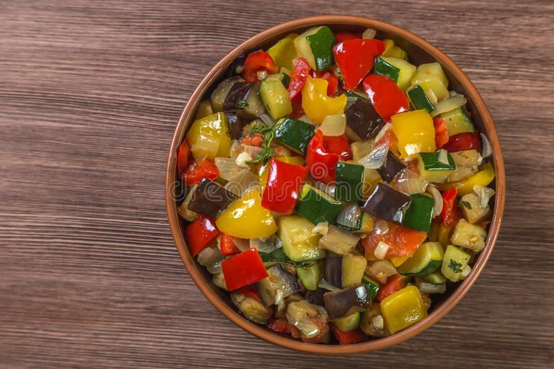 Provencal dish Ratatouille in a pot made of ceramics on the table made of oak planks. Brown. Proper nutrition and diet concept. Br. National dish of French stock photos