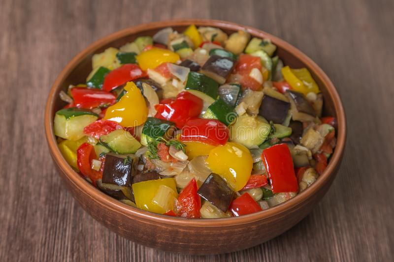 Provencal dish Ratatouille in a pot made of ceramics on a table of oak planks closeup. Brown. Proper nutrition and diet concept. B. National dish of French royalty free stock photography
