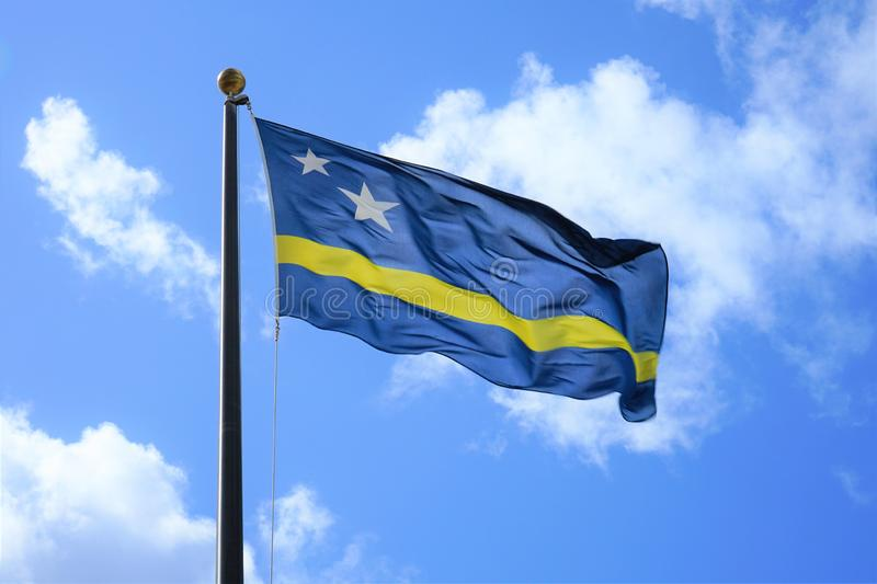 National flag of Curacao. Antilles, background, blue, clouds, country, curacao, dutch, fabric, flag, flag pole, government, illustration, island, nation, nationa stock photo