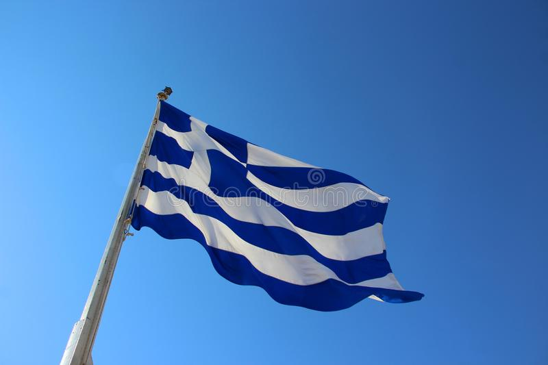 Flag of Greece with the cloudless blue sky in the background. The national flag of Greece, popularly referred to as the `sky-blue-white` or the `blue-white` royalty free stock photos