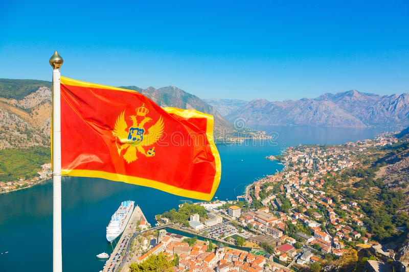 National flag of Montenegro waves in Boka Kotorska bay, Montenegro. National flag of Montenegro waves in the wind close up. Red and yellow Flag of Montenegro on stock image