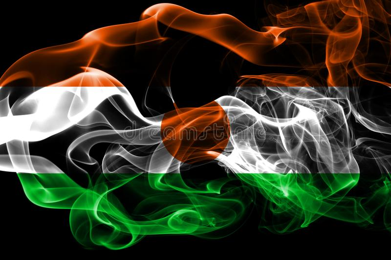 National flag of Niger made from colored smoke isolated on black background. Abstract silky wave background. National flag of Niger made from colored smoke stock images