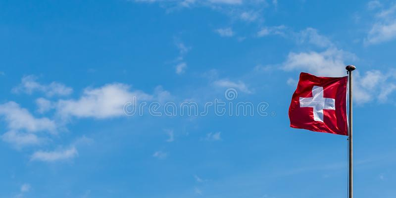 The national flag of Switzerland. Waving in the wind against blue sky and white clouds royalty free stock photography