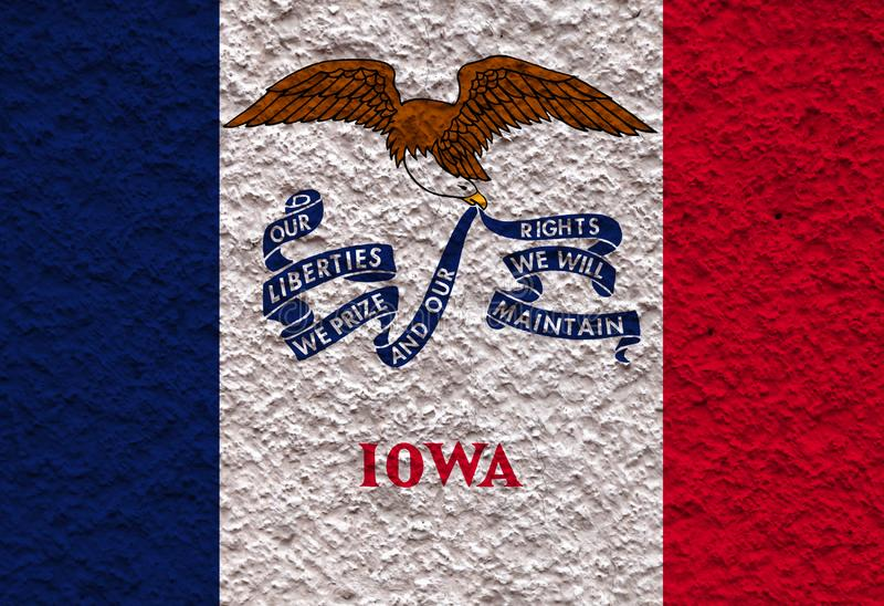 The national flag of the US state Iowa in against a gray wall with stony surface on the day of independence in colors of blue red stock photo