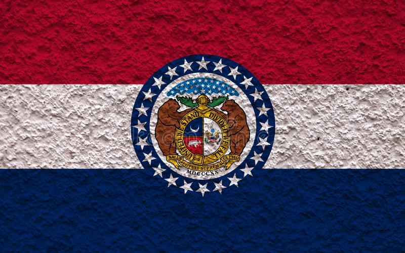 The national flag of the US state Missouri in against a gray wall with stony surface on the day of independence in blue red and royalty free stock photo