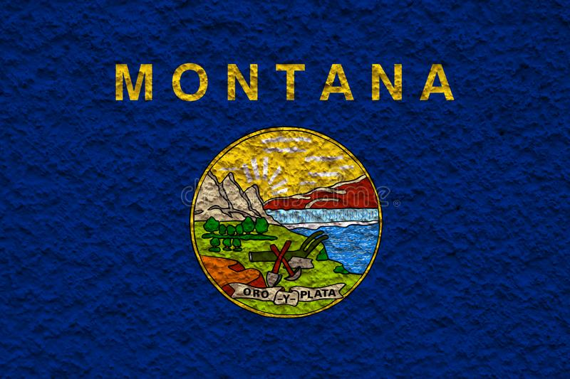 The national flag of the US state Montana in against a gray wall with stony surface on the day of independence in colors of blue royalty free stock photo