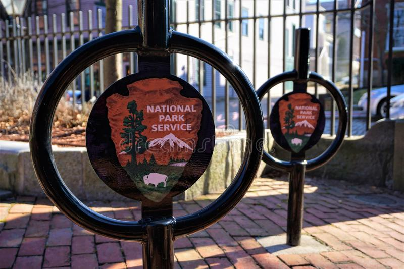 National Park Service emblems New Bedford Massachusetts. Two NPS emblems are stamped on a pair of black painted bicycle stations to lock up and protect. Marking stock photo