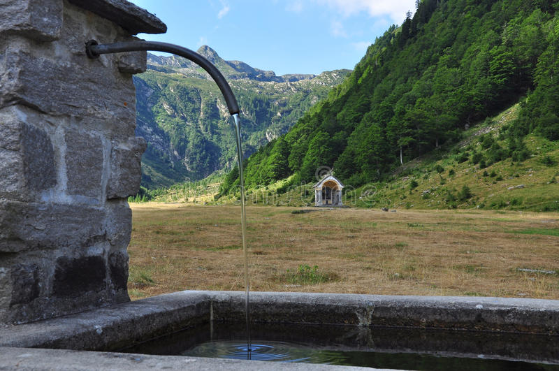 National park Val Grande, Italy. Log water fountain. Italian national park Val Grande. Traditional mountain log water fountain. Mountain landscape by blue sky royalty free stock photography