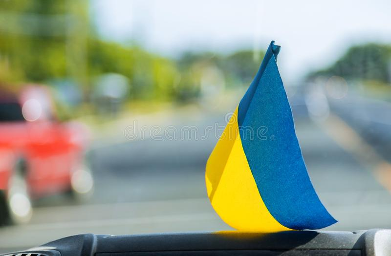 National symbol. Blue-yellow flag of Ukraine. Patriotic sign on glass inside the car. National patriotic symbol. Blue-yellow flag of Ukraine on glass inside the royalty free stock image
