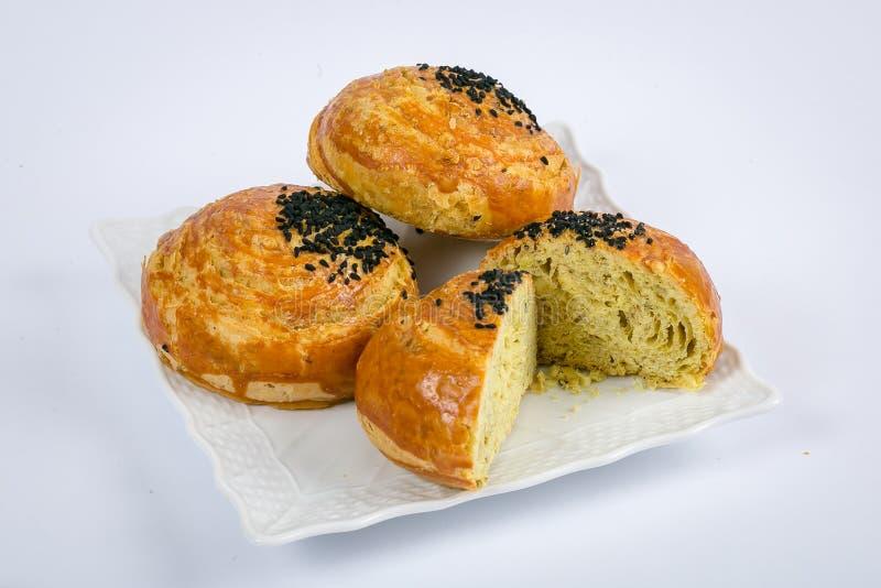 Nationale gebakjes Vier niet zoet roze die broodjesbladerdeeg met zwarte komijnzaden wordt bestrooid die op een witte porseleinpl stock afbeeldingen