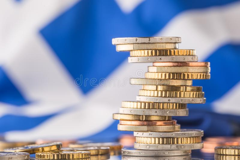 Nationale vlag van Griekenland en euro muntstukken - concept Euro muntstukken De EU stock foto