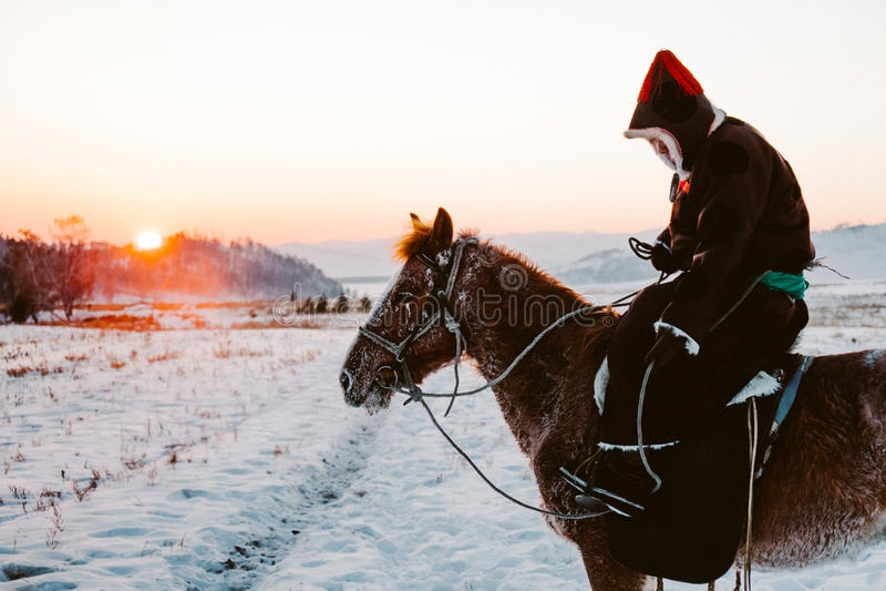Nationaler asiatischer Reiter mit Pferd auf einem Sonnenuntergang stockfotografie