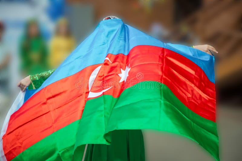 Nationaler Zeichenhintergrund Das Mädchen legte ihm eine Fahne auf die Schulter Aserbaidschanische Tradition patriotisch Windflas lizenzfreie stockbilder
