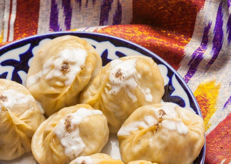 Nationales manti Lebensmittel des Usbeks auf traditionellen Gewebe adras stockfotos