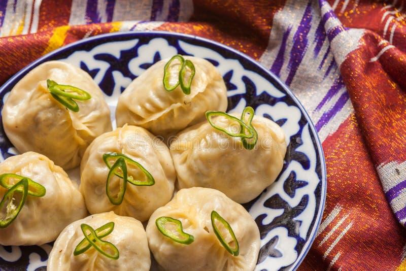 Nationales manti Lebensmittel des Usbeks auf traditionellen Gewebe adras stockfotografie