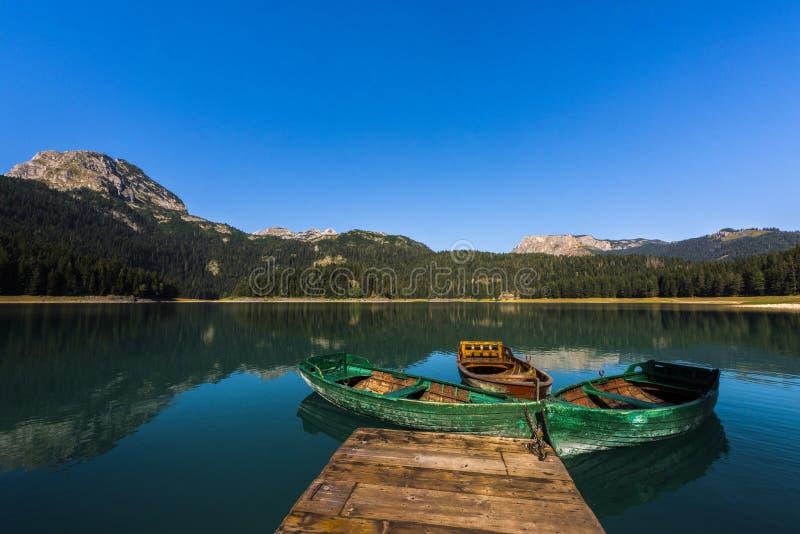 Nationalpark Durmitor - Mountainsee Black See ` Crno-jezero ` mit hölzernen Booten und Reflexionen des Gebirgszugs im klaren Wass lizenzfreie stockbilder